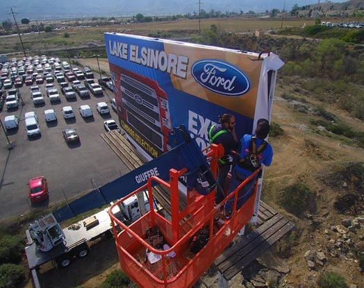lake elsinore ford billboard being worked on by crane